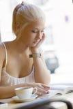 Attraktive junge Frau liest Buch am Café Lizenzfreie Stockbilder