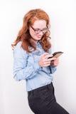 Attraktive junge Frau mag, was sie auf dem Smartphone sieht Stockbild