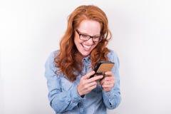 Attraktive junge Frau mag, was sie auf dem Smartphone sieht Stockfotos