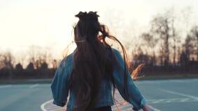 Attraktive junge Frau mit dem sehr langen Haar, in der Jeansabnutzung, die in Richtung zum hellen Sonnenlicht läuft, wendet sich  stock video footage