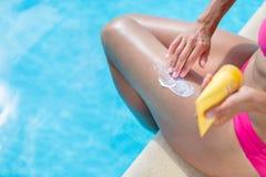 Attraktive, junge Frau mit der gesunden Haut, die suncream anwendet Stockfotos