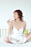 Attraktive junge Frau mit einem grünen Apfel und einem gla stockfoto