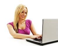 Attraktive junge Frau mit einem Laptop, der am Schreibtisch sitzt Stockbilder
