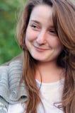 Attraktive junge Frau mit einem unterhaltenen Lächeln lizenzfreie stockbilder
