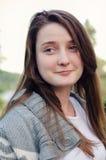 Attraktive junge Frau mit einem unterhaltenen Lächeln lizenzfreies stockbild