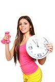Attraktive junge Frau mit einer Uhr und Dumbbells auf einem weißen BAC Stockfoto
