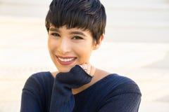 Attraktive junge Frau mit freundlichem Lächeln des kurzen stilvollen Haares stockfotografie