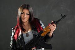 Attraktive junge Frau mit Gewehr Stockfotos