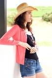 Attraktive junge Frau mit Hut draußen anstarrend Stockfotos