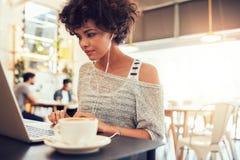 Attraktive junge Frau mit Kopfhörern unter Verwendung des Laptops am Café stockbilder