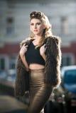 Attraktive junge Frau mit Pelzkap im städtischen Modeschuß. Schönes modernes junges Mädchen mit eng anliegender Kleidung Lizenzfreie Stockbilder
