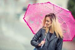 Attraktive junge Frau mit rosa Regenschirm im Regen und im starken Wind Mädchen mit Regenschirm im Herbstwetter Stockfoto
