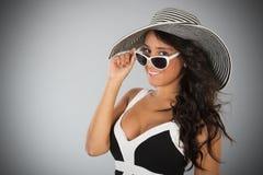 Attraktive junge Frau mit Strohhut und Sonnenbrille Stockfoto