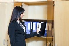 Attraktive junge Frau nehmen einen Ordner mit Dokumenten vom Kabinett Stockfoto