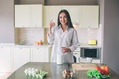 Attraktive junge Frau steht in der Küche und in der Aufstellung Sie betrachtet Kamera und das Lächeln Mädchen hält Schale Milch i lizenzfreie stockfotografie