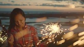 Attraktive junge Frau tanzt mit Wunderkerze am Abend, Zeitlupe stock video