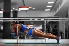 Attraktive junge Frau tut Plankenübung beim Ausarbeiten in der Turnhalle Lizenzfreies Stockbild