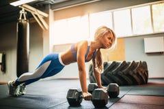 Attraktive junge Frau tut Plankenübung beim Ausarbeiten in der Turnhalle Lizenzfreie Stockfotos