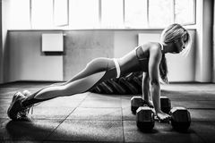 Attraktive junge Frau tut Plankenübung beim Ausarbeiten in der Turnhalle Stockfotos