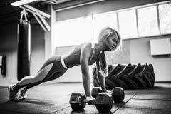 Attraktive junge Frau tut Plankenübung beim Ausarbeiten in der Turnhalle Lizenzfreie Stockbilder
