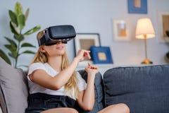 Attraktive junge Frau in VR-Kopfhörer gestikulierend und lächelnd Lizenzfreie Stockbilder