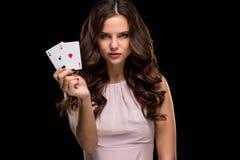 Attraktive junge Frau, welche die gewinnende Kombination von Pokerkarten hält Stockfotos