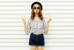 Attraktive junge Frau, welche die roten Lippen senden s??en Luftku? im schwarzen runden Hut, kurze Hosen, wei?es gestreiftes Hemd lizenzfreie stockbilder