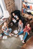 Attraktive junge Frauen, die zusammen studieren und an der Kamera lächeln Lizenzfreies Stockbild
