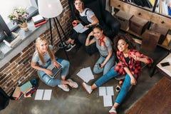 Attraktive junge Frauen, die zusammen studieren und an der Kamera lächeln Lizenzfreie Stockfotos