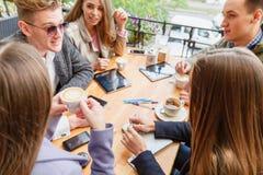 Attraktive junge Freunde, die am Café auf einem unscharfen Hintergrund sich entspannen schwarzes Telefon mit Empfänger Stockbild