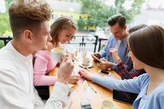 Attraktive junge Freunde, die am Café auf einem unscharfen Hintergrund sich entspannen schwarzes Telefon mit Empfänger Stockfotos
