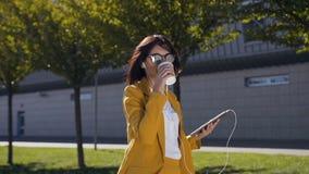 Attraktive junge Geschäftsfrau in der Sonnenbrille trinkt Kaffee während sie eine Mitteilung auf Tablet-Computer sendend draußen stock video