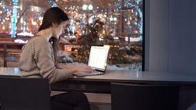 Attraktive junge Geschäftsfrau, die an dem Laptop sitzt an der Bar, äußere Winternachtstadt verziert für Weihnachten arbeitet Lizenzfreies Stockbild