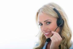 Attraktive junge Geschäftsfrau, die einen Telefon-Kopfhörer verwendet Lizenzfreies Stockfoto