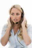Attraktive junge Geschäftsfrau, die einen Telefon-Kopfhörer verwendet Lizenzfreie Stockfotos