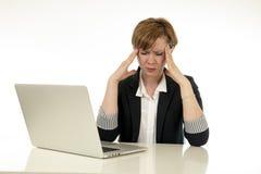 Attraktive junge Geschäftsfrau, die an ihrem Computer betont, ermüdet und überwältigt arbeitet lizenzfreie stockbilder
