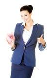 Attraktive junge Geschäftsfrau, die Sparschwein hält und O zeigt Stockfotos