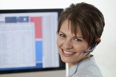 Attraktive junge Geschäftsfrau mit einem Kopfhörer Lizenzfreie Stockfotografie