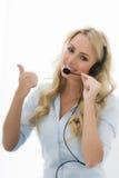 Attraktive junge Geschäftsfrau, die einen Telefon-Kopfhörer verwendet Stockfoto