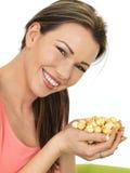 Attraktive junge glückliche Frau, die eine Handvoll des Toffees beschichtet hält stockfotos