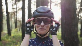 Attraktive junge kaukasische Frau setzt die weg Radfahrengläser, die schwarzen Sturzhelm und Trikot tragen Triathlonkonzept stock video