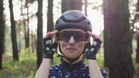 Attraktive junge kaukasische Frau setzt die weg Radfahrengl?ser, die schwarzen Sturzhelm und Trikot tragen Triathlonkonzept Langs stock video footage