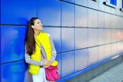 Attraktive junge lächelnde Frau, die nahe einer blauen Wand steht Stockfoto