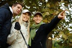Attraktive junge Leute, die beim Waldlächeln wandern Lizenzfreie Stockfotografie