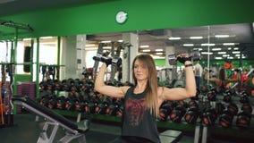 Attraktive junge muskulöse Frau, die in der Turnhalle trainiert und mit Dummkopf ausarbeitet stock video