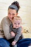 Attraktive junge Mutter, die ihr kleines Baby umarmt Lizenzfreies Stockfoto