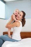 Attraktive junge Mutter, die nettes Baby im Schlafzimmer hält Stockfotografie