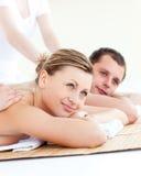 Attraktive junge Paare, die eine rückseitige Massage empfangen Lizenzfreies Stockbild