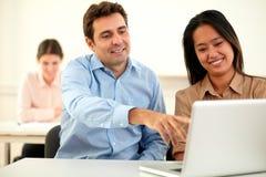 Attraktive junge Paare, die an Laptop arbeiten Stockfotos