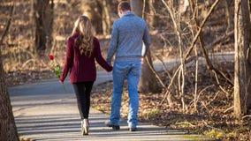 Attraktive junge Paare, die weg von Zuschauer auf Weg gehen Stockbilder